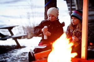 Ellinor Danielsson och Maja Sillanpää passade på att fika vid elden.