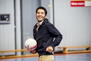 Habib Habibi hjälper ungdomar spela fotboll.