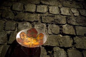 Elna Joloms glas verkar i en formtradition från Jugend och Art Noveau, en frodig växtornamentik där överdådet är norm, inte undantag.