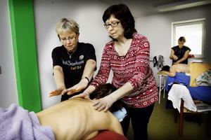 Monica Andersson får instruktioner av Marianne Joelsson i hur rörelserna över Karin Bergströms rygg ska utföras.