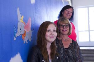 Isabelle Andersson (längst fram i bild) var en av tre elever på Bromangymnasiet som fick uppdraget bildläraren Christina Stål (i mitten) att göra en väggmålning i Västra skolans huvudentré. Initiativtagare var Mia Lindqvist (längst bak i bild), fritidspedagog på Västra skolan.