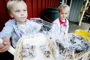 VAKTAR KAKORNA. 4-åringarna Isak Björk och Malin Åström hade full koll på fikautbudet. Barnen har hjälpt till att baka allt och det fanns många olika sorters kakor att välja mellan.