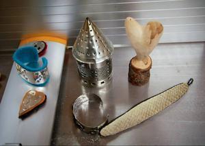 Plåtsmycken och en plåtlykta där materialet består av från konservburkar och krympta ullplagg.