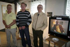 Initiativtagarna Anders Andrée, Rolf Jönsson och Göthe Jönsson under öppningen av utställningen om Yngve Gamlin.  I tv-bilden ses Gamlin själv.