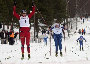 Stina Nilsson sträcker armarna i skyn i en segergest. Bakom forsar Evelina Settlin fram mot JSM-silver