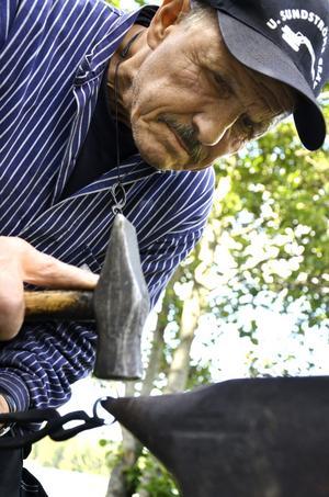 Göran Jansson som driver klensmedjan i Åsboberg på plats och smider under Larsmäss, här utvidgar ut en besökares järnring.