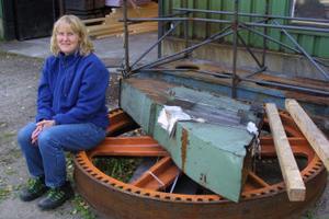 Anna-Karin Pettersson, produktionschef, vid svänghjulet till smideshammaren från 1932. Om några veckor ska det vara monterat - och sno.