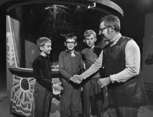Vi i femman startade i SR redan 1963. 1970 började även SVT sända frågesportprogrammet. Programledaren Carl-Uno Sjöblom gratulerar de tävlande i klass 5 i Västra Skolan i Hallsberg (Håkan Dunder, Göran Björklund och Jan Månsson) som vann  riksfinalen 4:e oktober 1970 i Stockholm.