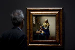 En man tittar på Vermees målning Kökspiga som häller upp mjölk.