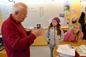 Författare. Arne Norlin visar ett korttrick för Elin Hagberg och Anni Hartin i klass 5 B.