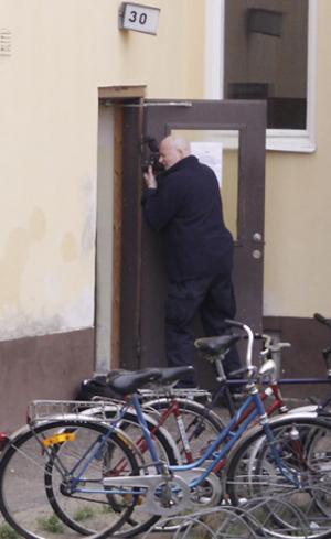 Polisens tekniker fotograferade in i dörröppningen, där den omkomna kvinnan bodde.