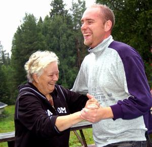 Medhjälparen Kerstin Eriksson och fäbodbrukaren Täpp Lars Arnesson tar sig en svängom i duggregnet på fäbodvallen. Foto:Anders Mojanis