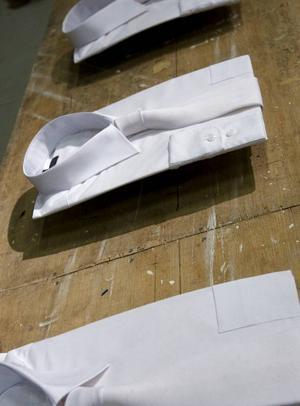 Peter Kruses skjortor ser ut att sväva fritt över bordet.Reaktiv skuptur med luftpistol och ballong av Peter Hagdahl.