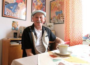 Gösta Jansson i Borlänge samlar på 1950-talet. Bordduken är tidstypisk liksom kaffekoppen. Köksgardinerna är gjorda av plast.