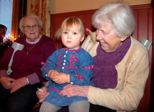 Karin Sars, 85 år och Elsa Eriksson, 81 var äldsta deltagarna på julgransplundringen. Elsa har barnbarnsbarnet Tilde i knäet.