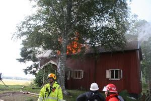 Räddningsledare Svante Nordström kommenderar brandmännen till rätt plats. Bakom ser man huset i full brand.