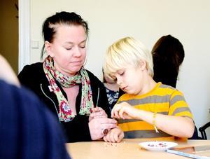Här ska du se. Läraren Eva Ohlsson hjälper Albin Hägerström att slutföra arbetet med ett armband. I bakgrunden Maria Lindberg.
