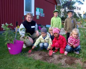 Siv Emretson med några av barnen i trädgården där de planterar hallonbuskar.
