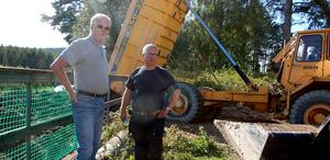 Lars Collin och Jack Gottling diskuterar schaktarbetet vid dammen.