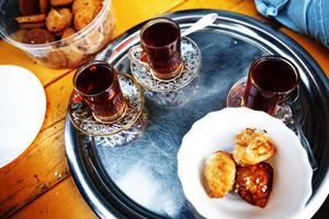 Saina Abdul–Hassan kommer ut med en fulladdad tebricka. Sött arabiskt te och hemgjorda friterade logame–kakor.