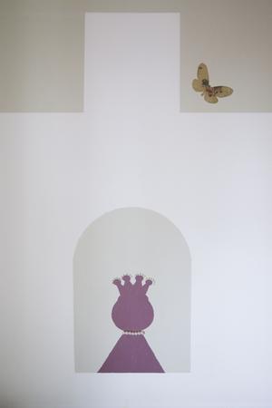 Med fantasi. En prinsessa tittar ut genom slottsfönstret, pärlor fyndade på loppis är limmade direkt på väggen, liksom fjärilen.