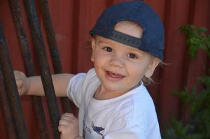 En liten lycklig kille, mitt barnbarn Liam, bakom en faluröd ladugård i Kärrbo, spelade med sina upphittade stenar på rostiga järnrör.