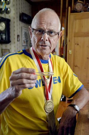 Små klimpar. Stig Söderlund har både guldmedaljen och guldslipsen runt halsen. I plaströret finns de små, små korn som gav honom vinsten i VM. Foto: Elin Kjellin