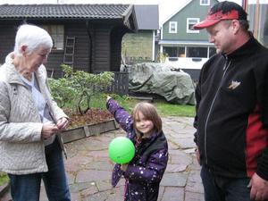 Tove Wessling pekar på taket där ballongen med brevet låg i torsdags. Marga Olsson och pappa Tomas Wessling tittar på.