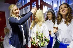 Luciamamman Anna Sörensson tar bort stearin ur lucian Anna Sundqvists hår.