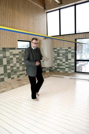 """Satsning inte i hamn. Nya bassängen med höj- och sänkbart golv skulle bli ett lyft för Hallsberg. Men än så länge går den back, även om den fina anläggningen prisas av allmänheten. Här en bild från invigningen när kommunalrådet Thomas Doxryd """"gick på vattnet"""". Arkivbild: Barbro Isaksson"""