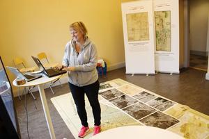 Margareta Fryk, processutvecklare på Lantmäteriet hjälper till att projicera gamla kartor, med fastighetsgränserna inritade, på en TV-skärm.