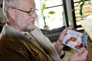 Nyblivne morfar Evert visar stolt upp ett av livets många glädjeämnen; bilden på lilla dotterdottern som föddes för en månad sedan.
