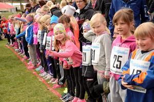 Spänning. Uppradade på startlinjen står de yngre flickorna. De är taggade och väntar lite otåligt på att startskottet ska gå. Tjejerna ska springa tusen meter i terrängen för att gå i mål på Smedsvallen.
