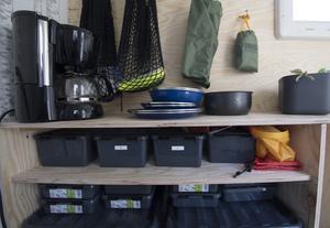 Längs ena långsidan i huset löper en bänk med hyllor och på väggen hänger muggar och påsar i karbinhakar. Här finns det mesta som behövs på liten yta.