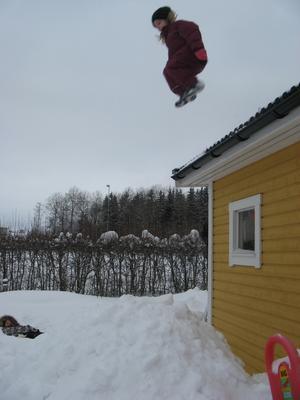 När vi skottade ner snö från taket på boden så blev det en lockande snöhög nedanför. Här är det Wilma, 6 år, som gör