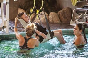 Annamy Rindmyr och Esmeralda Orellana lyfter ner rullstolsburne Fredrik Öjersson i bassängen.
