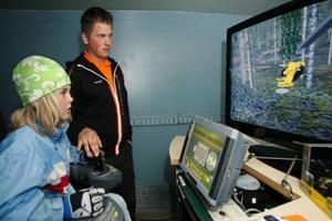 Anna Backman, 8 år, testade att köra skogsskördare i en  simulator. Calle Svedling, som pluggar på Älvdalens naturbruksgymnasium, hjälpte henne att hitta alla knappar.