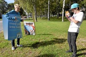 """Modell. En kasserad valaffisch vid vägkanten blev till """"valkläder"""" för Erik Nordin och Adam Isaksson förevigade fotodmodellen med sin mobilkamera. Foto: Jan Wijk"""