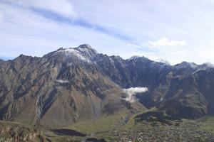 Vyn från 2000 meters höjd med bergstopp och byn Stepantsminda nedanför.   Foto: Mimmi Granat