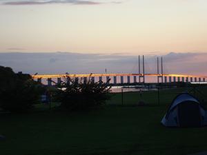 Vi fick husvagnsplats med denna härliga vy. Bilden är tagen på kvällen med solljuset som lyser på bron.
