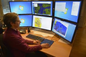 Meteorolog bland många datorskärmar.