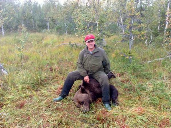 Omar Jonsson med sin första björn, som han fick skjuta efter en dramatisk jakt, då han var så nära björnen att den bet honom i handen.  Foto: Berne Brenje