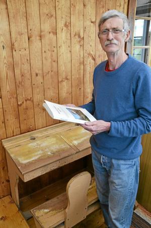 Jan Myrtorp har precis hämtat ut ett provexemplar av sin bok om Binninge skola. Skolbänken i bakgrunden kommer just från skolan i Binninge.