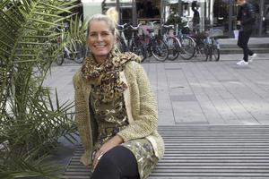 Annelie Eriksson bär grovstickad ulltröja i mjuk-limegrönt, mossgrönmönstrad klänning,  bohemisk bomullsilkesjal från Noa Noa.