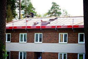 Utländska entreprenörer jobbar med att lägga nya tak på hyreshusen i bostadsområdet Hedslund i Rättvik.