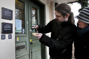 Calle Eklund, som har hjälpt till med QR-koderna till Kulturpromenaden, demonstrerar för kommunantikvarie Pia Hilborn hur man scannar av QR-koderna.