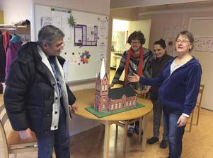 Konstnären Lalzim Halimi överlämnar modellen till prästen Eva Brolin (till höger) och kyrkorådets Barbro Berger. På bilden finns också konstnären fru Majlinda Halimi (i mitten).