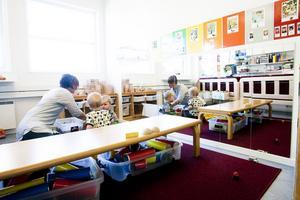 Förskollärare Ann Norin sitter på golvet i legohörnan tillsammans med Oscar och David.
