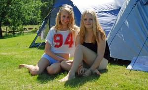Izabella Hedström, 16 år, och Linnea Liljeqvist, 15 år kommer från Stockholm sitter i gräset utanför sina tält och väntar på att maten ska serveras.