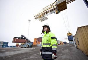 TRUCKAR OCH KRANAR. Det är ständigt liv och rörelse i containerterminalen i Gävle hamn. Truckar och kranar lastar och lossar oupphörligt containrar till och från båtar, tåg och bilar. Erica har jobbat här i fem år och har full koll på var kollegorna befinner sig och vad de gör för ögonblicket.